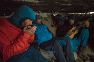Sean Villanueva, Nico Favresse and Seibe Vanhee play music to pas the time while waiting out a storm in the Belgium bivy cave near the base of the Torres. Torres del Paine, Patagonia, Chile.