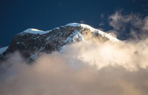 Evening light breaks through clouds illuminating the summit of Husacaran Norte. Cordillera Blanca, Peru. Photo by Steve Byrne