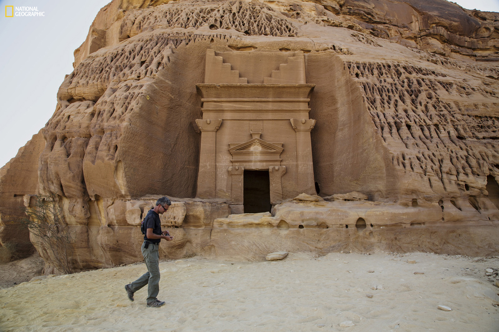 Paul Salopek wanders through the ancient Nabataean ruins of Madain Salih, carved into sandstone outcrops some 2,000 years ago. These structures were used as tombs for the wealthy during the Nabataean era. The kingdom stretched from its capital Petra in Jordan south to Madain Salih in the Hejaz region of present-day Saudi Arabia. Photo shows a tomb façade in the Al Khuraymat area of Madain Salih. Join the journey at outofedenwalk.org.Photograph by John Stanmeyer / National Geographic