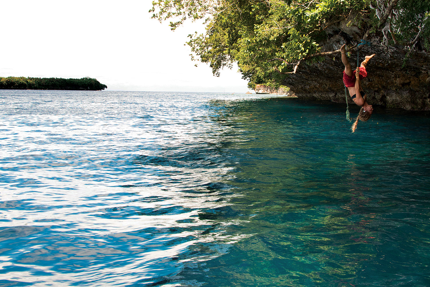 With a huge smile and belly laughs, Charlotte shows her acrobatic prowess on a rope swing hung by children from a nearby village. The turquoise water below hides an extraordinary reef wall for snorkeling and diving, while manta rays frequently migrate through the deep channel beyond.