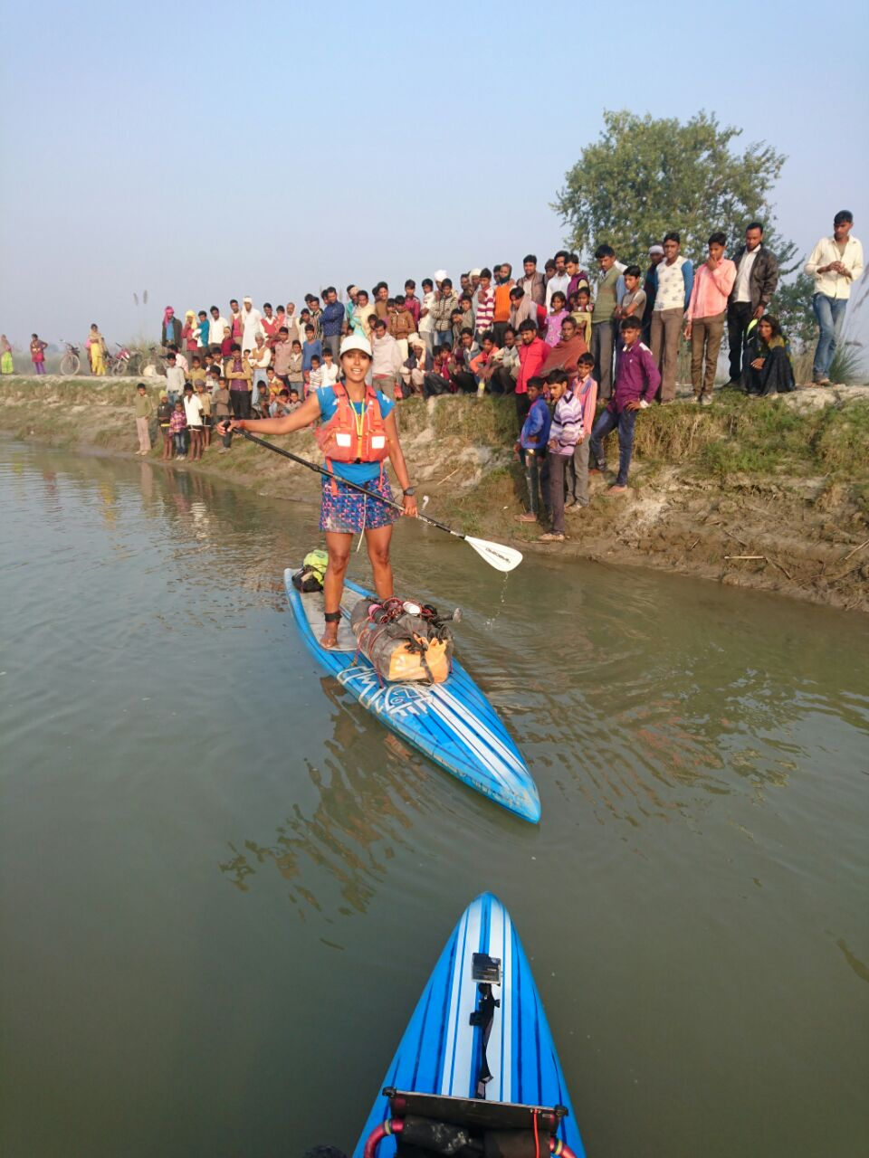 Men and boys see the team paddle off in the morning in Uttar Pradesh. Photo © Pascal Dubois