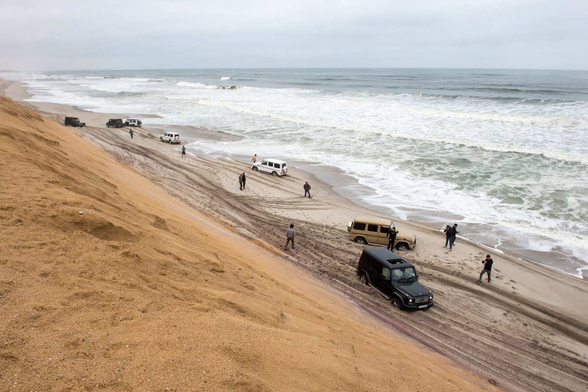 Six Mercedes Benz G-class SUVs find themselves trapped in deep sand, with the tide coming in on one side, and steep sand dunes on the other. We probably have less than 30 minutes to dig out all vehicles and get them turned around and up through a passage in the dunes. Photo: Dmitry Sharomov