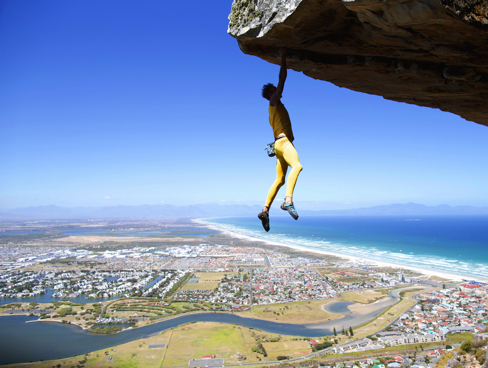 Dancing on the Ceiling (5.11d/7a). Hanging five on the first free solo ascent of 'Dancing on the Ceiling' (5.11d/7a). Muizenburg. Cape Town. Photographer: Stefan Grey.