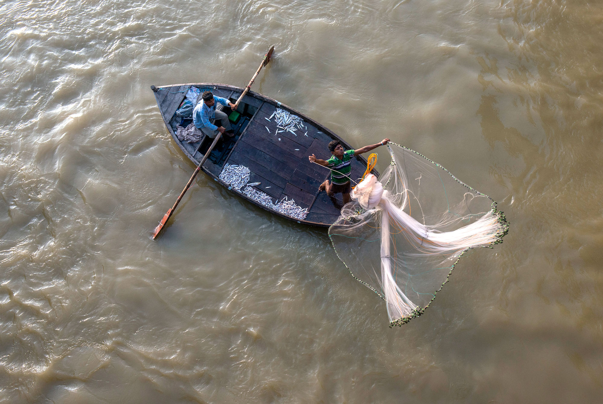 Above Kanpur, India, fishermen test their luck below an irrigation / flood weir. Most regions of the Ganges forbide fishing in its sacred waters but a Muslim community in the Kanpur region, see the river as an economic oppurtunity despite tails of toxic waters.
