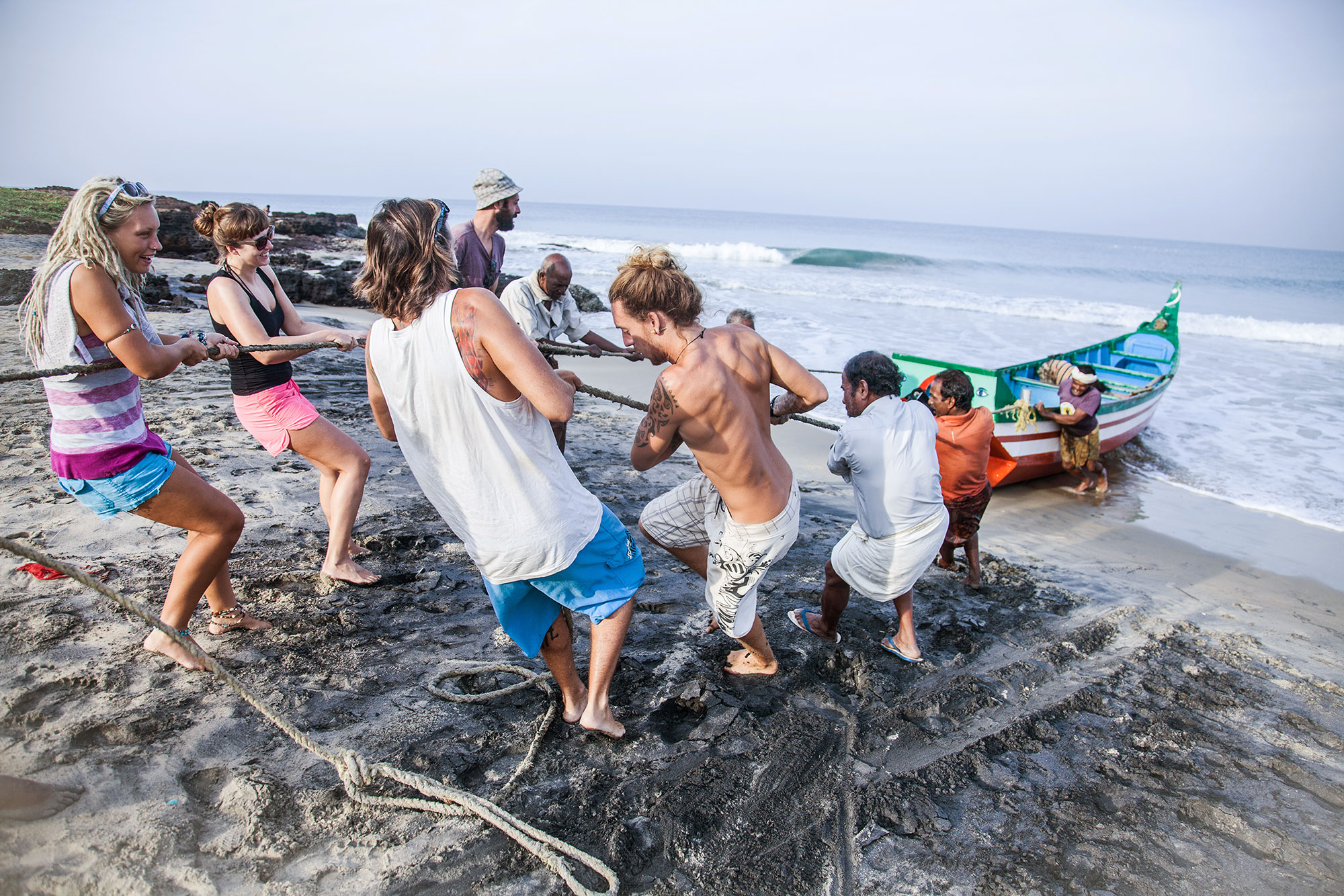 Surfers help fishermen drag their boat to the shore. PHOTO: Berta Tilmante