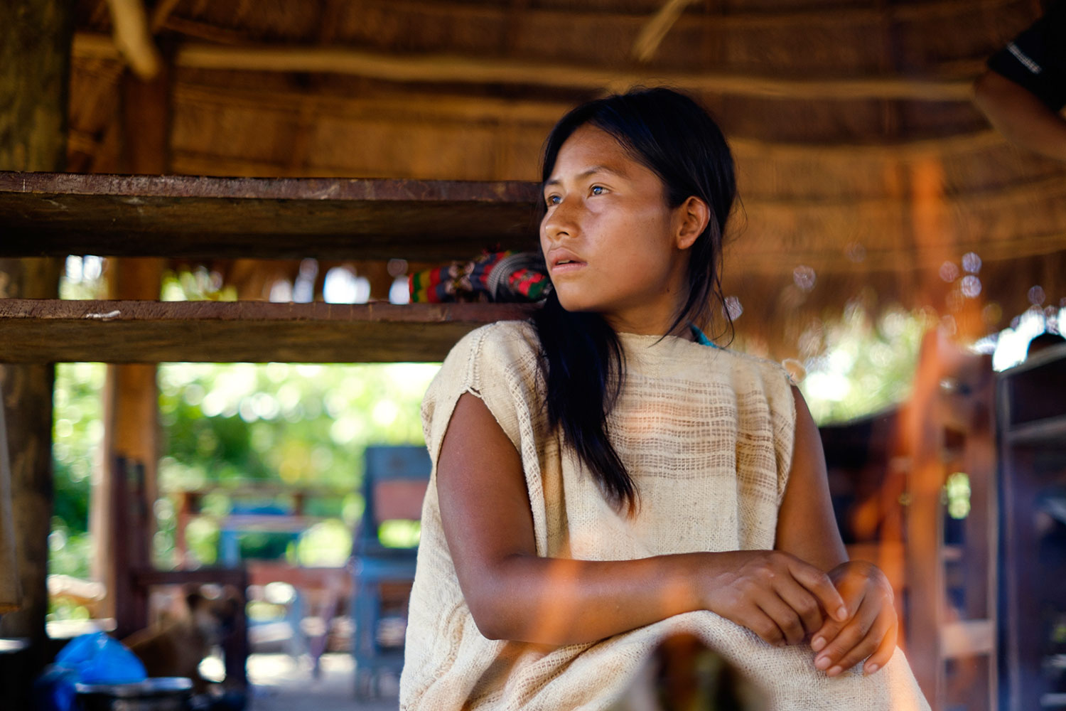 A young Matsigenka woman prepares a meal of Amazonian catfish steamed in bamboo shoots. She wears a traditional cushma while she works with her mother, but takes it off when she heads to the nearby schoolhouse for lessons. Photo: Kevin Floerke